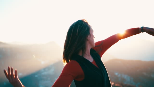 Young woman dancing on mountain top at sunrise  sleeve stock videos & royalty-free footage