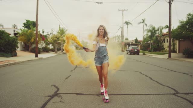 young woman dancing outside on roller skates with smoke grenade down city street - łyżwa filmów i materiałów b-roll