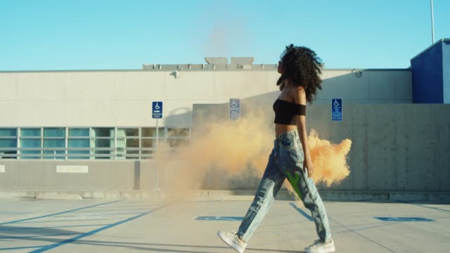 Young woman dancing outside with smoke grenade at sunset on rooftop parking garage