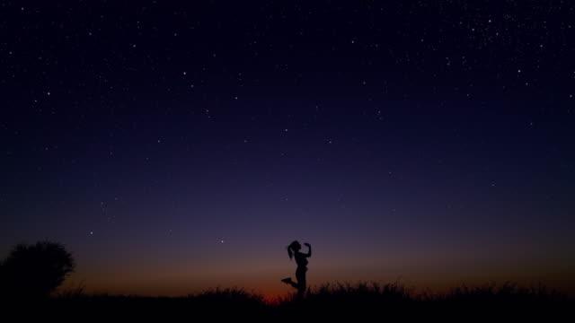 młoda kobieta tańcząca pod gwiaździstym niebem - niebo zjawisko naturalne filmów i materiałów b-roll