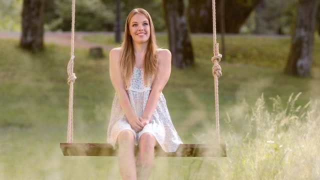SLO MO DS Young woman daydreaming on a swing Slow motion medium dolly shot of a young woman in a summer dress sitting on a swing in meadow and daydreaming. outdoor play equipment stock videos & royalty-free footage