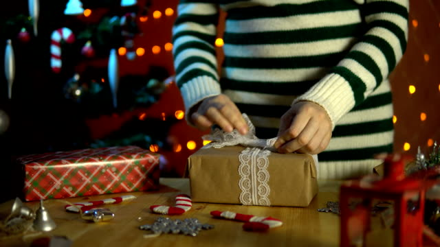 Young woman decorates a white bow with a gift box. video