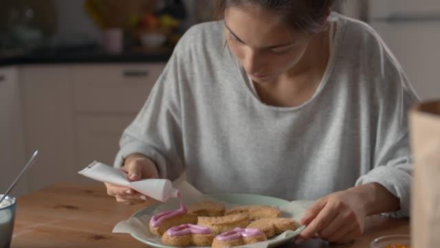 junge frau dekorieren handgemachte cookies - zuckerguss stock-videos und b-roll-filmmaterial