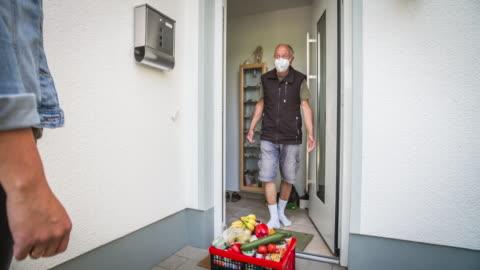 vidéos et rushes de jeune femme livrant des épiceries à la porte avant d'un homme aîné pendant la quarantaine de coronavirus - assistant