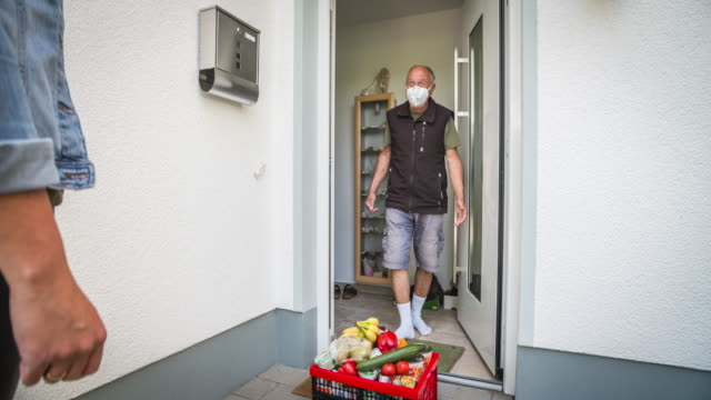 young woman delivering groceries to front door of a senior man during coronavirus quarantine - vicino video stock e b–roll