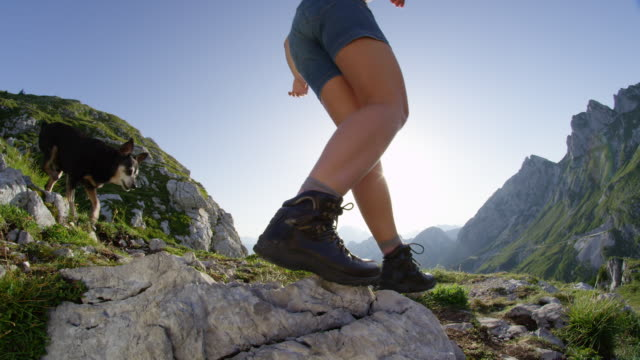 SLOW MOTION CLOSE UP: Young woman descends down a mountainside with her dog. video