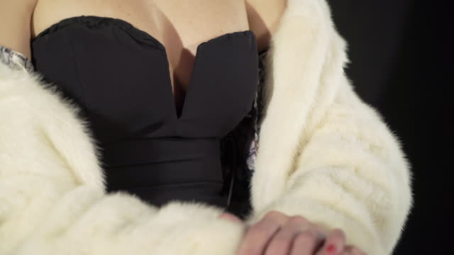 Young woman displays her cleavage in a short black body hugging dress video