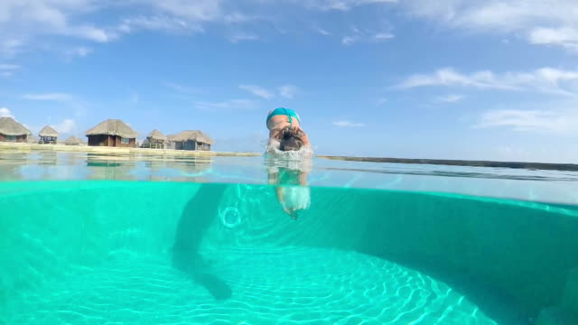 UNDERWATER: Young woman diving into swimming pool at luxury resort video