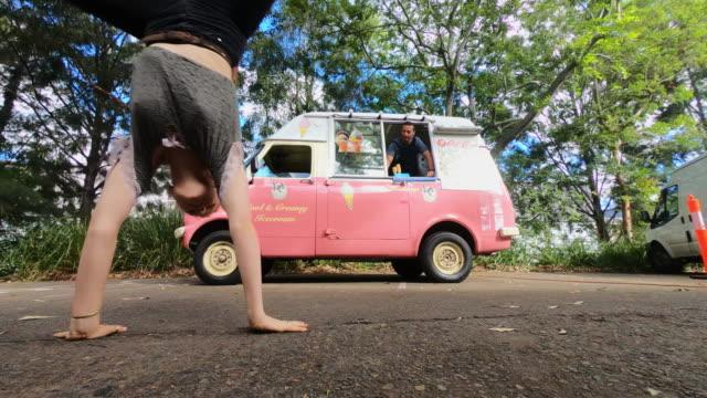 stockvideo's en b-roll-footage met jonge vrouw doen een radslag voor een vrachtwagen icecream - foodtruck