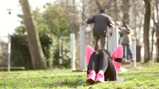 Young woman doing abs exercises at park video