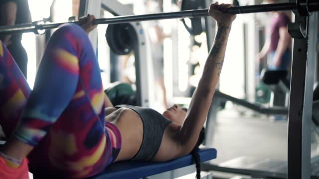 young woman doing bench presses with weights - kulturystyka filmów i materiałów b-roll