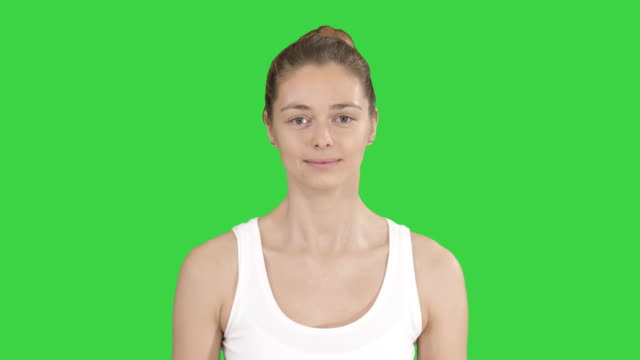 Young woman doing breathing exercise on a Green Screen, Chroma Key