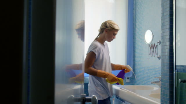 Young woman doing chores and cleaning bathroom at home Housework and domestic lifestyle, woman doing chores in bathroom at home, cleaning wash basin and tap with spray detergent. dishwashing liquid stock videos & royalty-free footage