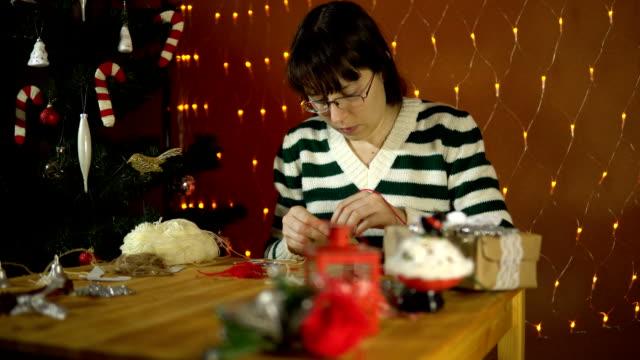 Jeune femme faisant un décor pour un arbre de Noël à côté des feux électriques jaunes. - Vidéo