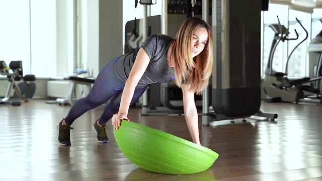 young woman doing exercise on bosu ball - metodo pilates video stock e b–roll