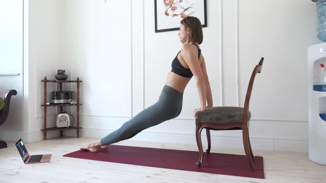 Young woman doing exercises at home video