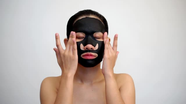 young woman doing facial black mask sheet with purifying mask on her face on white background - facial stock videos & royalty-free footage