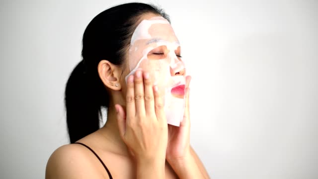 young woman doing facial mask sheet with purifying mask on her face on white background - face mask stock videos & royalty-free footage