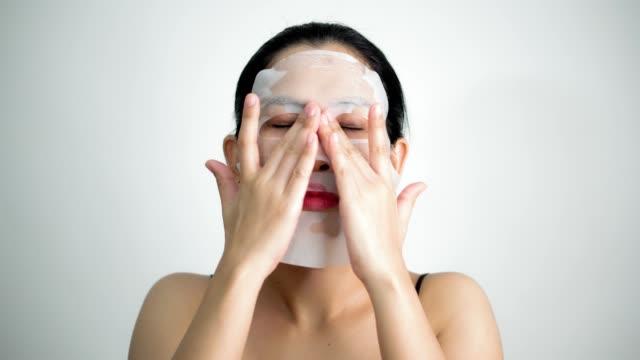 vidéos et rushes de jeune femme faisant des feuille de masque du visage avec masque sur son visage sur fond blanc - soin spa