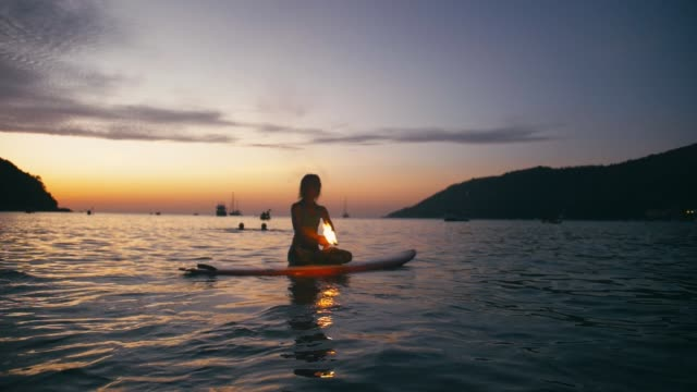 Young woman doing fireshow fire breathing perforrmance on sup board with paddle at sunset