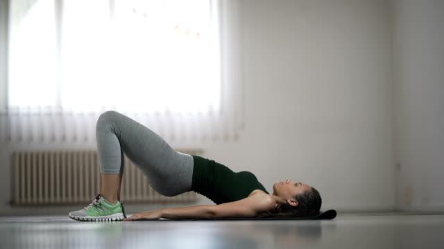 ヒップ リフト自宅を行う若い女性 - 有酸素運動点の映像素材/bロール
