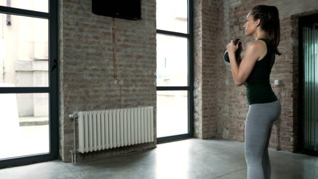 vídeos de stock e filmes b-roll de young woman doing kettlebell goblet squats - agachar se
