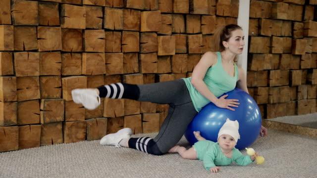 vídeos de stock e filmes b-roll de young woman doing lateral crunches on ball near little baby indoors - mulher balões