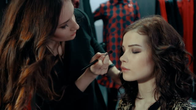 Young woman doing makeup on a model in the boutique of women's clothing. A young girl stylist applies to the eyelids of the brunette model a dark eye shadow with a special brush in the boutique with a large cabinet full of hangers with women's clothes. beautician stock videos & royalty-free footage