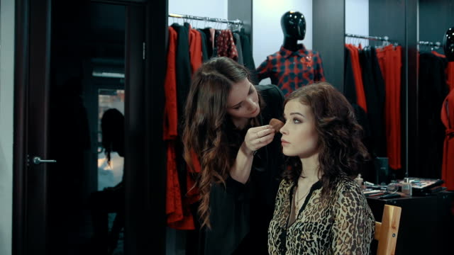 Young woman doing makeup on a model in the boutique of women's clothing. Young woman doing makeup on a model in the boutique with a large cabinet full of hangers with women's clothes. beautician stock videos & royalty-free footage