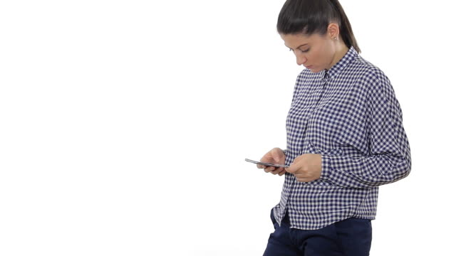 Young woman doing online shopping with the mobile phone. Young woman doing online shopping with the mobile phone. White background. gold card stock videos & royalty-free footage