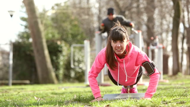 Young woman doing push ups exercises at park video