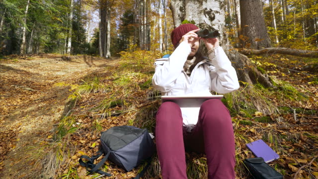 Young woman doing research in the forest. video