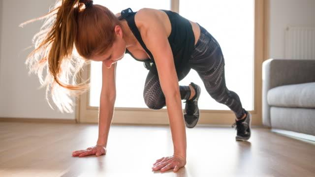 young woman doing running plank workout - odzież sportowa filmów i materiałów b-roll