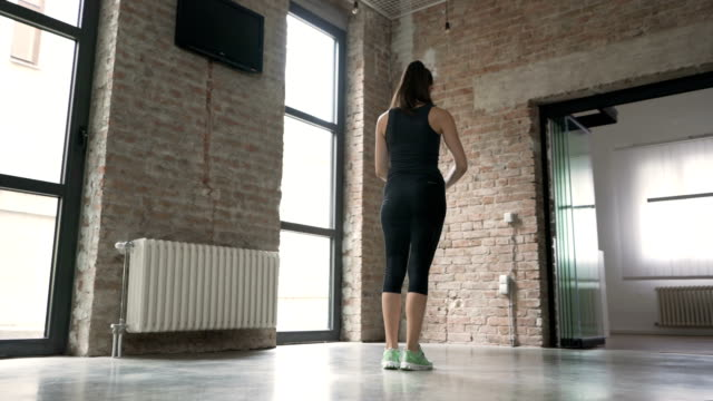 Young Woman Doing Side Lunges Young woman doing side lunges at home. stepping stock videos & royalty-free footage