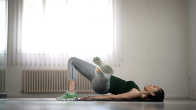 単一の足の股関節を行う若い女性を持ち上げる - 有酸素運動点の映像素材/bロール