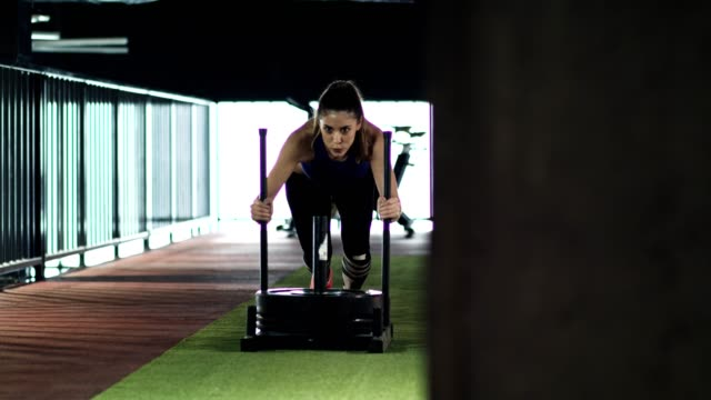 Young woman doing sled pushes in the gym