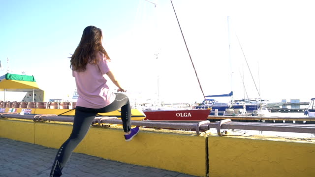 Young woman doing sport exercises at sunlight with yachts on background video