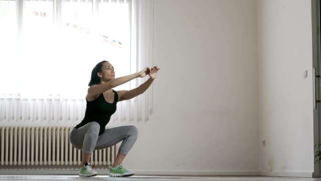 vídeos de stock e filmes b-roll de young woman doing squats - agachar se
