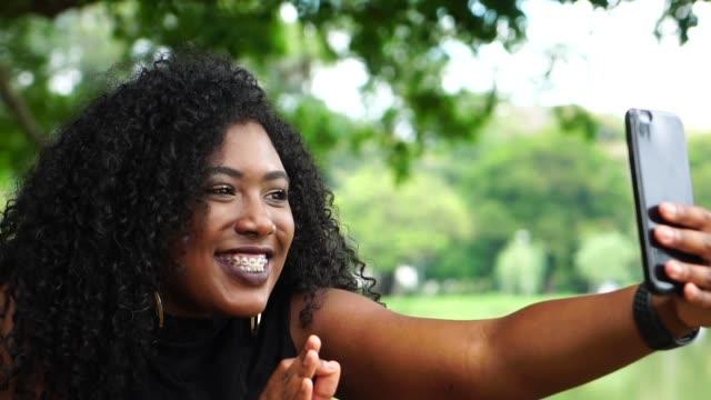 vídeos de stock e filmes b-roll de young woman doing video calling in the park - afro