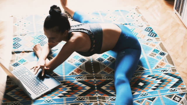 Young woman doing yoga and using a laptop at home Female yogi doing splits and stretching while using a laptop. Young Caucasian woman doing yoga at home. Learning exercise from tutorials on her laptop. Practicing meditation and breathing exercise at home. doing the splits stock videos & royalty-free footage