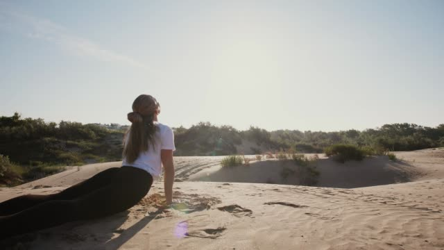 Young woman doing yoga asana at sunrise Upward-Facing dog pose. Morning practice