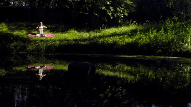 young woman doing yoga asanas on the river bank - posizione corretta video stock e b–roll
