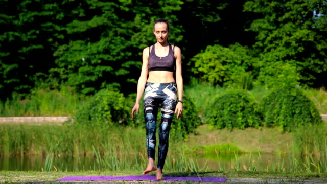 Young woman doing yoga exercise in green park Young woman doing yoga exercise in green park mental wellbeing stock videos & royalty-free footage