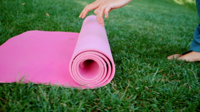 young woman doing yoga exercise - opening her pink yoga mat on green grass at the park. slow motion - tappetino video stock e b–roll