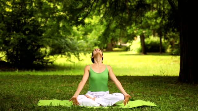young woman doing yoga exercise - lotusställning bildbanksvideor och videomaterial från bakom kulisserna