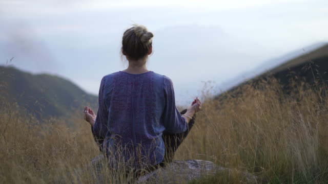 Young woman doing yoga in nature in tall grass on mountain top at sunset