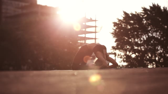 Young woman doing yoga meditating outdoors on a rooftop