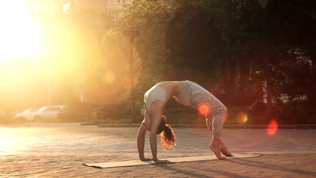 Young Woman Doing Yoga Meditation Exercises at Sunset