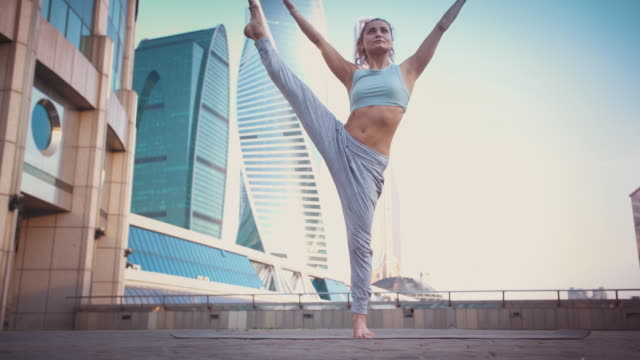 Young Woman Doing Yoga Meditation Exercises at Sunset Young Woman Doing Yoga Meditation Exercises at Sunset Against Modern Business Buildings. Stock video life balance stock videos & royalty-free footage