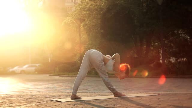 Young Woman Doing Yoga Meditation Exercises at Sunset